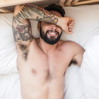 ベッドに横たわっている若い男の高い角度の光景