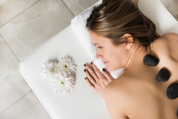 Высокий угол зрения молодая женщина, лежа на кровати, принимая массаж горячими камнями