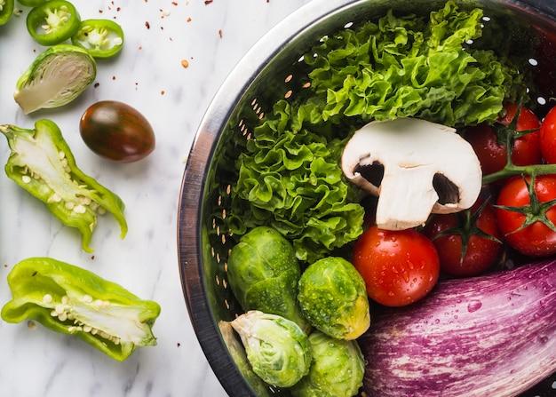 Взгляд высокого угла органических здоровых овощей в дуршлаге