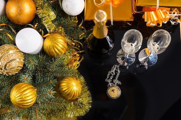 シャンパンのボトルと金で包まれたギフトとクリスマスボールと見掛け倒しで飾られた常緑の枝とグラスのペアと黒い表面のアンティーク懐中時計の高角度ビュー