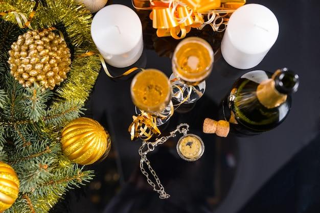 Старинные карманные часы под большим углом на столе, окруженном бутылкой шампанского и бокалами, белыми свечами и вечнозелеными ветвями, украшенными золотой гирляндой из мишуры и елочными шарами