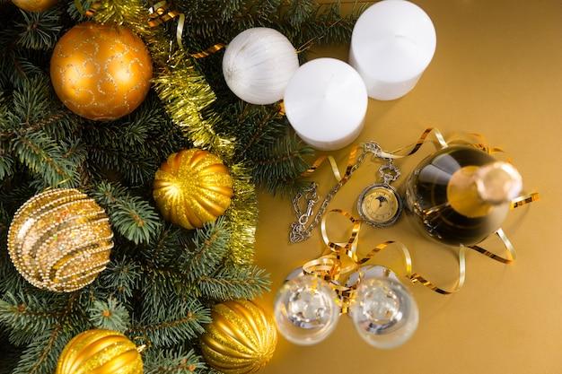 シャンパンとグラスのボトル、白い柱のキャンドルとゴールドのクリスマスボールと見掛け倒しのガーランドで飾られた常緑の枝と黄色の背景にアンティーク懐中時計の高角度ビュー
