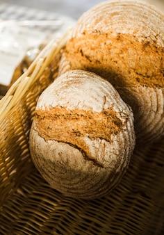 Взгляд высокого угла испеченного хлеба в плетеной корзине на стойле хлебопекарни