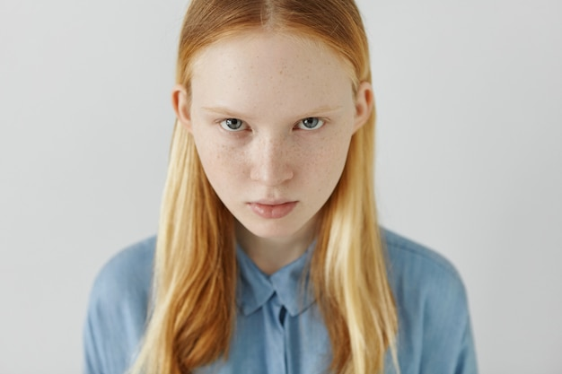 Взгляд высокого угла красивой очаровательной женщины нежного возраста смотря из-под светлых бровей. красивая девушка с веснушками в длинных светлых волосах заправлена за уши в синей рубашке