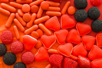 High angle view of berry fruits, heart shape and capsule candies