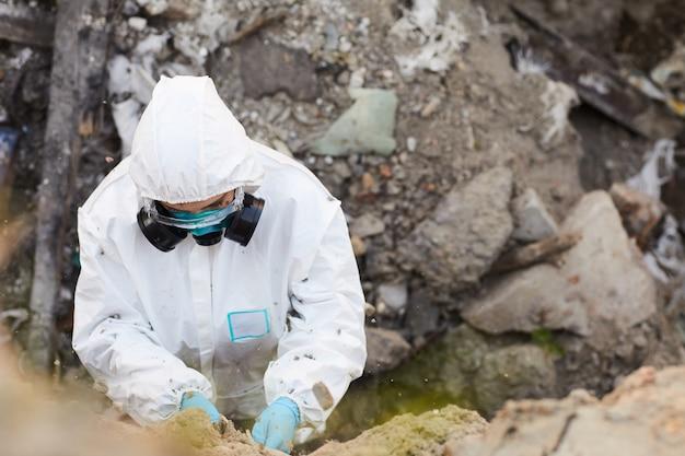 屋外の岩のサンプルを採取する防護服を着た生物学者の高角度ビュー