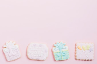 High angle view of birthday cookies on pink background