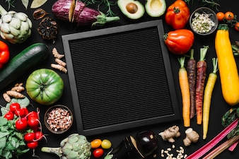 High angle view of black frame surrounded with various raw vegetables