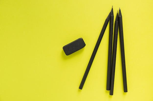 노란색 배경에 검은 연필과 지우개의 높은 각도보기