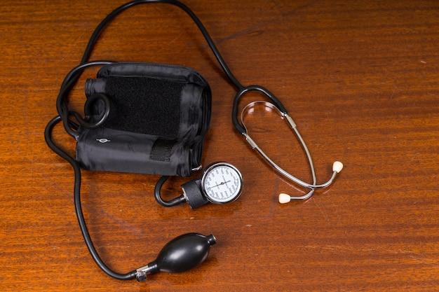 Высокий угол обзора медицинских принадлежностей для манжеты и стетоскопа артериального давления на деревянном столе с копией пространства