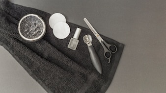 High angle view of body scrub; sponge; nail polish; scissors and callus remover on towel