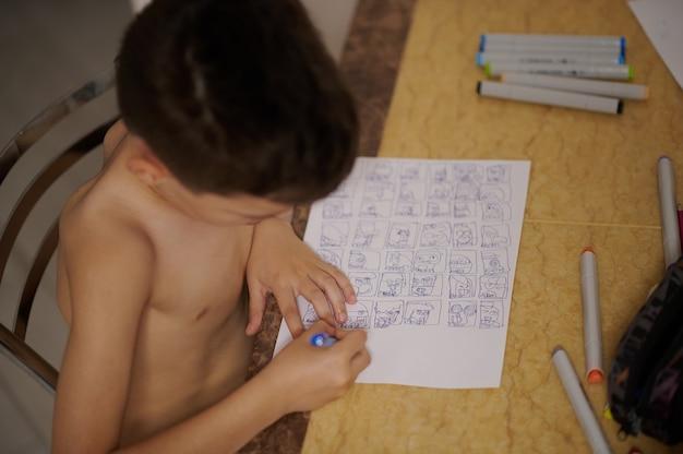 흰 종이에 만화와 만화를 그리는 테이블에서 소년의 높은 각도 보기