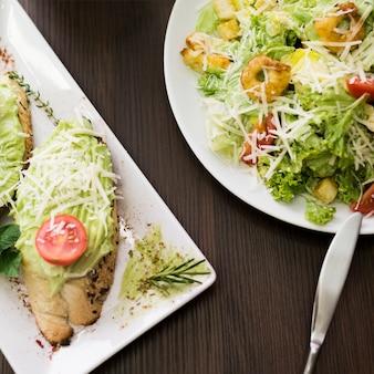 Высокий угол обзора хлеба с соусом песто; тертый сыр и помидор черри на тарелке возле салата над столом