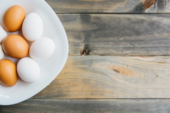 High angle view of brown and white eggs on plate on wooden surface