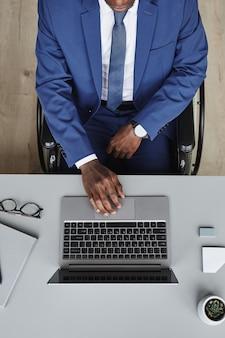 オフィスの彼の職場でラップトップでオンラインで作業しているスーツのビジネスリーダーの高角度ビュー