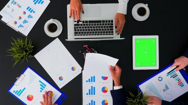 オフィステーブルの上の緑色の画面のクロマキータブレットと会議室のビジネスマンの高角度ビュー
