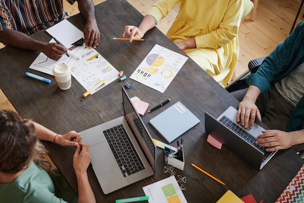 Высокий угол обзора деловых людей, сидящих за столом с документами и компьютером и работающих в команде на деловой встрече