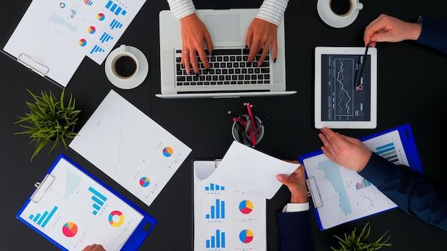 Высокий угол обзора бизнес-команды, работающей с финансовыми отчетами в корпоративном офисе за столом, анализирующим годовое планирование данных следующего проекта