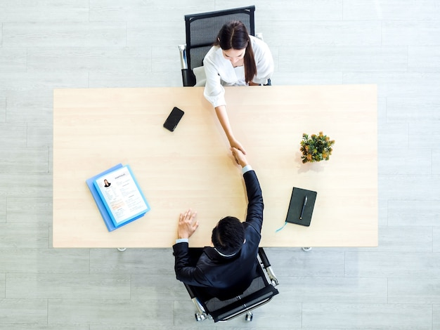 사무실에서 이력서 또는 이력서 서류와 함께 나무 책상 위에 여자 후보와 악수하는 소송에서 사업가의 높은 각도보기.