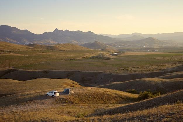 그림 같은 산 풍경에 캠프장의 높은 각도보기. 텐트와 흰색 차가 옆에 주차 된 언덕이 많은 지역에서 야영하는 관광객. 자연, 관광, 여행, 휴가 및 하이킹 개념