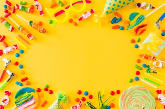 High angle view of candies; lollipops; candles; party at and blower on yellow surface