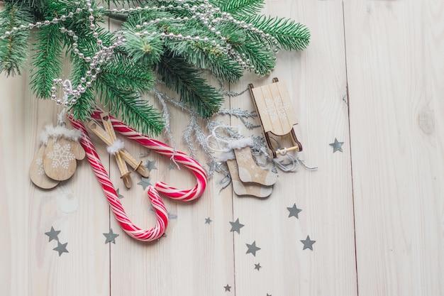 Высокий угол обзора леденцов в окружении рождественских украшений на деревянном столе