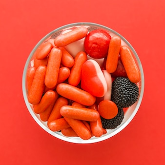 High angle view of carious sweet candies on red background