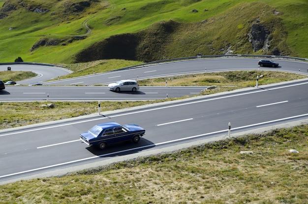 スイスの緑に覆われた丘に囲まれた曲がりくねった道の車のハイアングルビュー