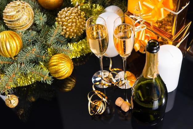 コピースペースと装飾された常緑樹の枝、白いキャンドル、ゴールドで包まれたギフトを備えた光沢のある黒い表面のシャンパンのハイアングルビュー