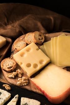 チーズの高角度のビュー。パンのスライスと木製の机の上のクルミ