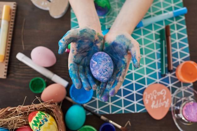 손에 색칠한 달걀을 들고 식탁에서 부활절 달걀을 그리는 아이의 높은 각도