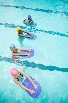 수영장에서 수영하는 동안 킥보드를 사용하는 어린이의 높은 각도보기