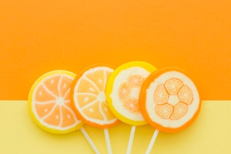 High angle view of citrus fruit candies on yellow and orange background