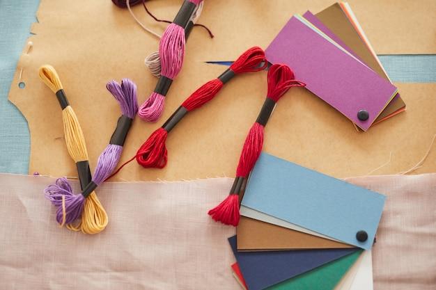 Высокий угол обзора цветных узоров с нитками, лежащих на столе в мастерской
