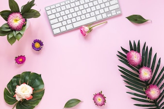 High angle view of colorful flowers and keyboard on pink background