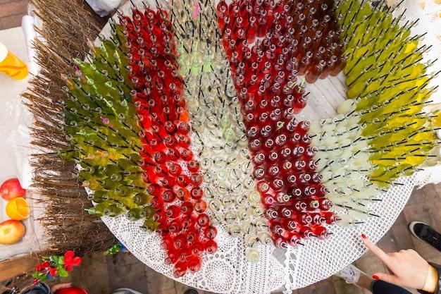 Разноцветные газированные напитки для гурманов, расположенные на столе с открытыми крышками и черной соломкой, на фестивале или мероприятии на открытом воздухе под высоким углом
