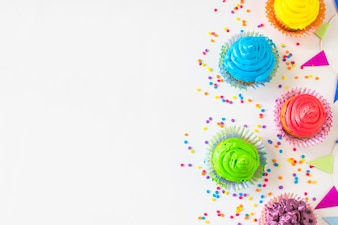 High angle view of colorful muffins and candies on white backdrop