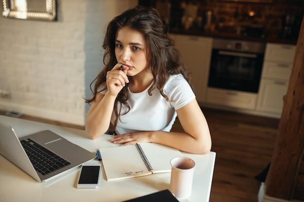 Высокий угол обзора сконцентрированной молодой женщины-учителя, сидящей за столом с портативным компьютером, держащей ручку с задумчивым выражением лица, готовящейся к онлайн-уроку, пишущей от руки в блокноте