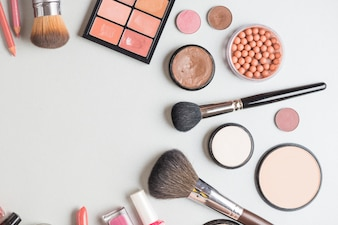 High angle view of cosmetic products on white backdrop