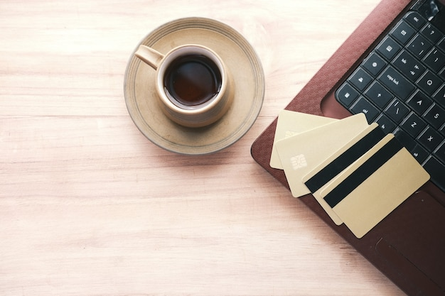 주황색 배경의 키보드에 있는 신용 카드의 높은 각도 보기