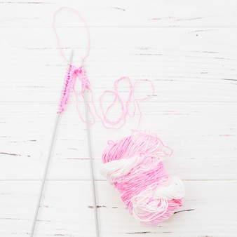 High angle view of crochet with pink yarn on wooden background