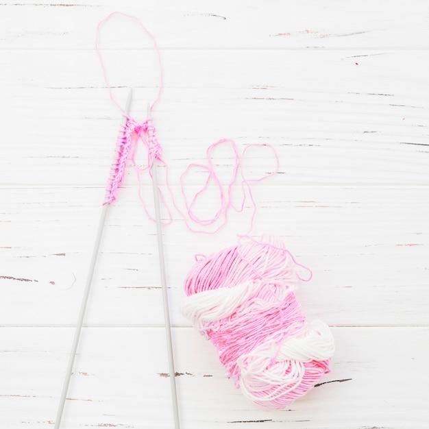 Высокий угол зрения вязание крючком с розовой пряжей на деревянном фоне