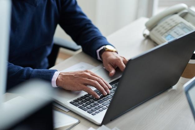ノートパソコンで仕事でトリミングされた従業員の高角度のビュー