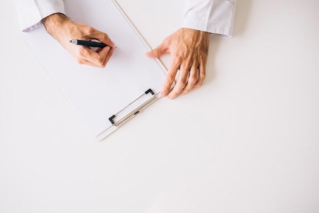 Высокий угол зрения руки врача на пустой белой бумаге