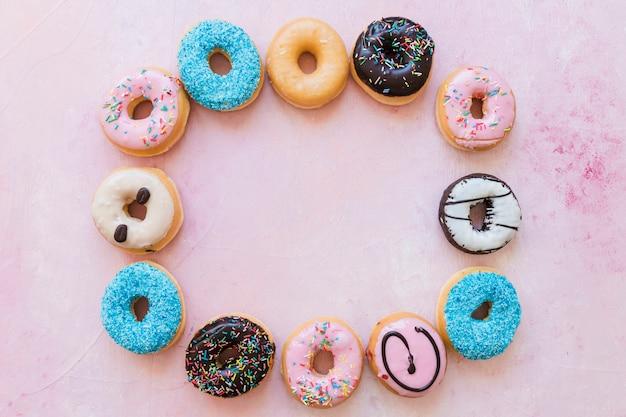 분홍색 배경에 프레임을 형성하는 도넛의 높은 각도보기