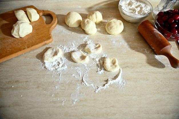 キッチンカウンターの生地と麺棒が散らばった小麦粉でキッチンカウンターの上に横たわっている木の板の高角度のビュー。餃子を段階的に調理するプロセス