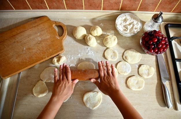 丸い餃子の型を作るためにキッチンカウンターの麺棒で生地を転がしている女性シェフの手の高角度ビュー。餃子を段階的に調理するプロセス。クローズアップ、食品の背景