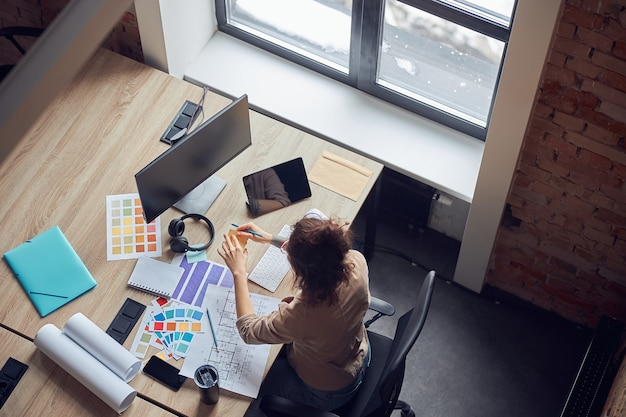 新しいインテリアデザインプロジェクトに取り組んでいる付箋を使用して女性デザイナーのハイアングルビュー