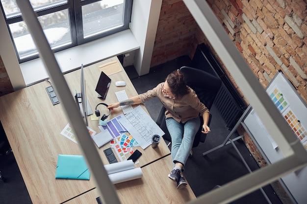 Высокий угол обзора девушки-дизайнера интерьера в наушниках, читающей план во время работы