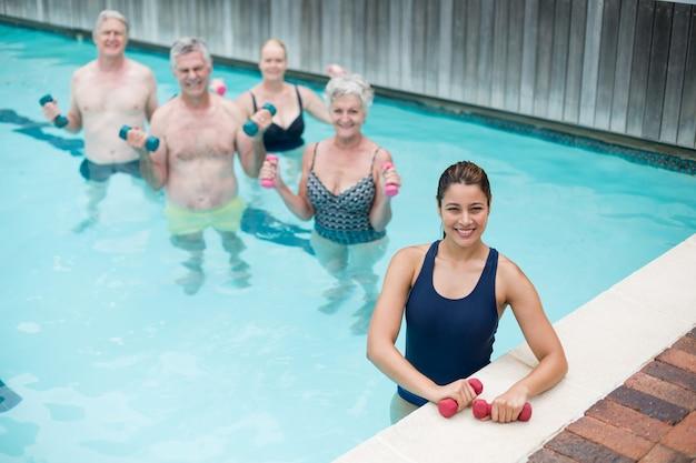 Высокий угол обзора девушки-тренера со старшими пловцами, стоящими в бассейне